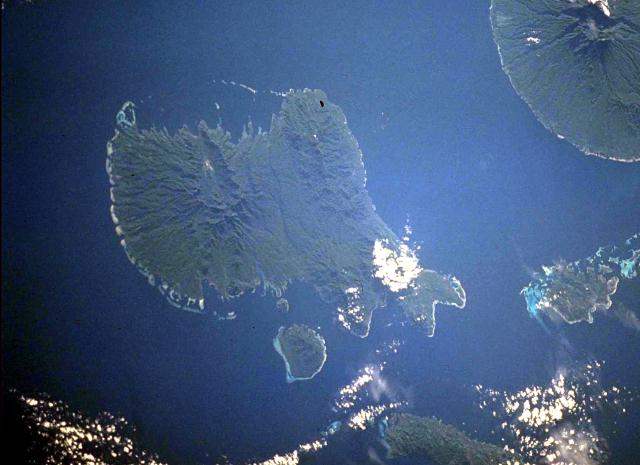 Vella Lavella Island (left center) in the New Georgia Islands in the Solomon Islands chain. North lies to the upper left in this NASA Space Shuttle image. Nonda volcano, the youngest volcanic feature of Vella Lavella Island, is a lava dome located within a well-preserved crater in the northern part of the island. The Paraso thermal area, the small light-colored area at the upper left-center portion of the island, displays solfataras, hot springs, and boiling mud pots. Kolombangara Island is at the upper right. (NASA Space Shuttle image ISS002-727A-2, 2001)