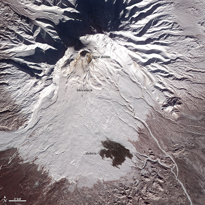 Shiveluch volcano on a Terra satellite image from 19 Feb 2012. Volcanic debris is seen on the lower flanks; the debris traveled about 10 kilometers (6 miles) from Shiveluch's growing lava dome. (Nasa Earth Observatory)